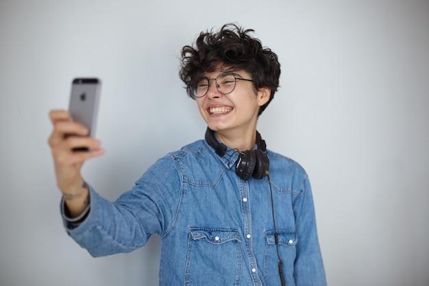 Счастливая молодая милая кудрявая брюнетка дама в очках держит смартфон в поднятой руке и весело улыбается в камеру, делая селфи, изолированные на белом фоне