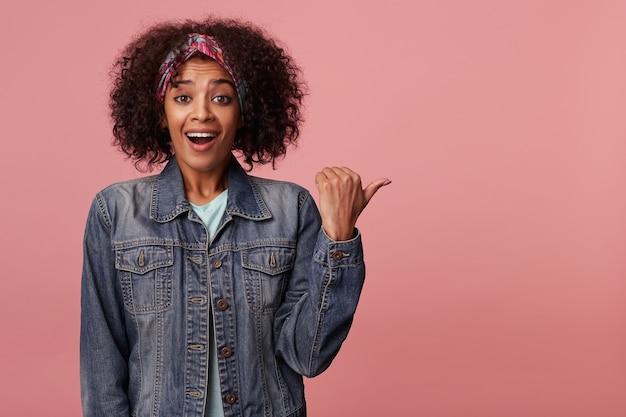 Счастливая молодая милая темнокожая женщина с короткими вьющимися каштановыми волосами позирует в яркой повязке на голову и джинсовом пальто, весело смотрит с возбужденным лицом