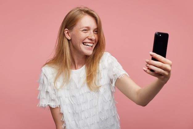 Felice giovane bella rossa femmina con acconciatura casual guardando allegramente la fotocamera del suo smartphone e sorridente ampiamente mentre fa selfie, in piedi su sfondo rosa