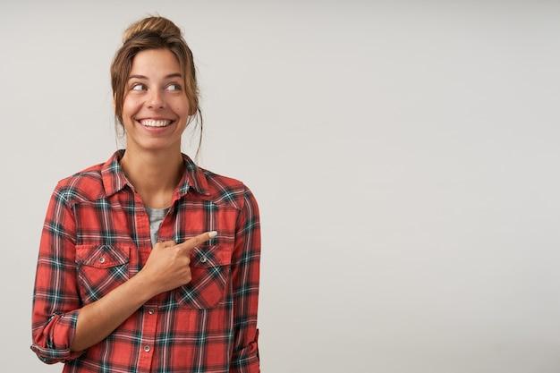 化粧なしでポーズをとって、人差し指を脇に向けて、広く笑って、いい気分になっているお団子髪型の幸せな若い素敵な女性