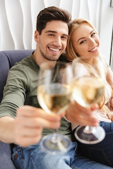 Happy young loving couple drinking alcohol white wine champagne.