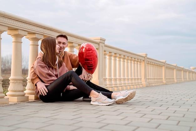 행복 한 젊은 사랑의 부부는 빨간 풍선을 들고 재미 공원에서 야외에서 서로 포용