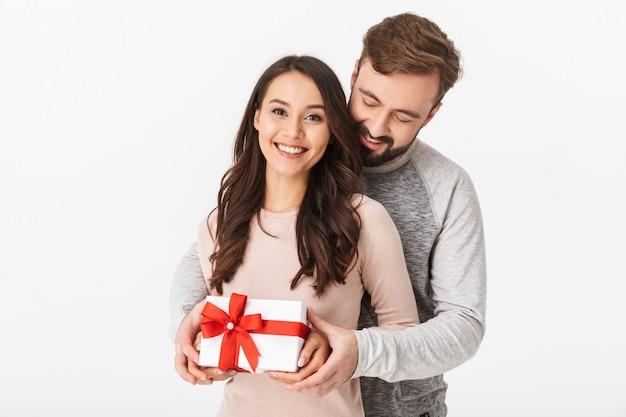 Счастливые молодые любящие пары держа коробку подарка присутствующую.