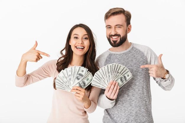 指しているお金を保持している幸せな若い夫婦