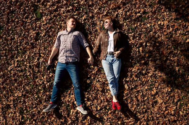 Happy young loving couple lying on the ground and holding hands in autumn park.