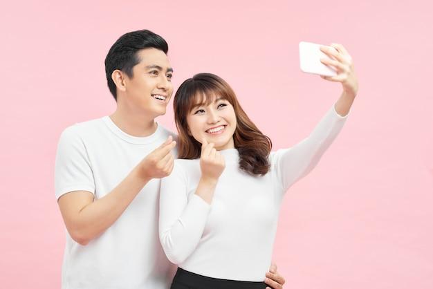 Счастливая молодая любящая пара делает селфи и улыбается, стоя на сером фоне