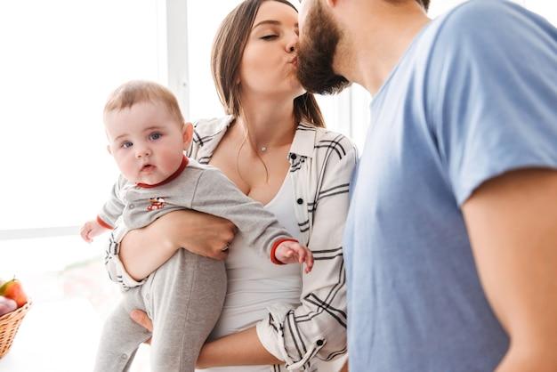 幸せな若い夫婦の両親のキス