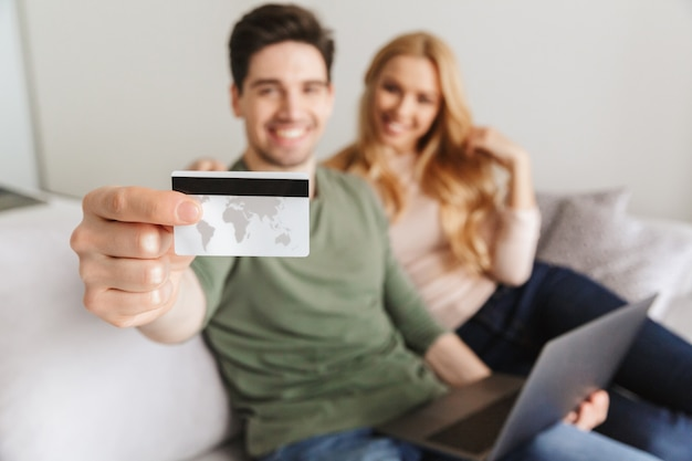 Happy young loving couple sitting on sofa holding debit card.