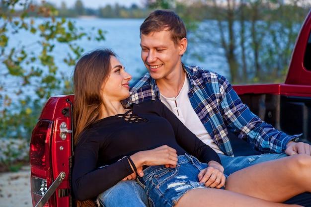 湖の近くのビーチで赤い車の後ろに笑みを浮かべて抱き締めて幸せな若い愛情のあるカップル。若いカップルが車の近くで抱擁します。