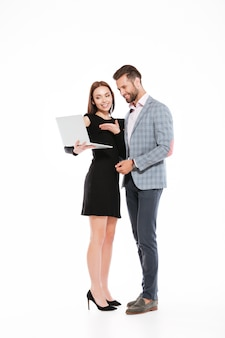 Happy young loving couple standing isolated using laptop computer.