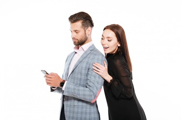Happy young loving couple standing isolated