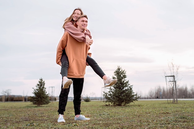 Счастливая молодая влюбленная пара в капюшонах, обнимая друг друга на открытом воздухе в парке, веселится