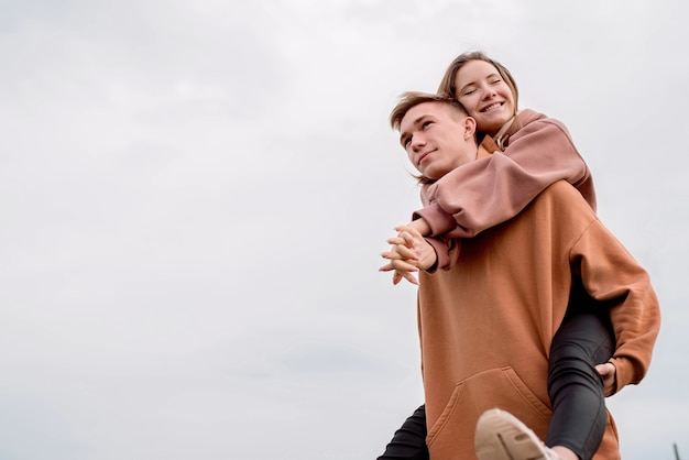 Happy young loving couple wearing hoods embracing each other outdoors in the park having fun on sky background