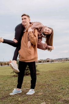 Happy young loving couple wearing hoods embracing each other outdoors in the park having fun