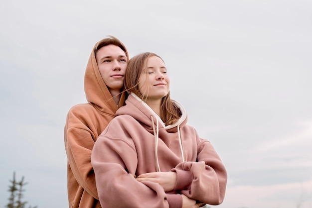 Happy young loving couple wearing hoods embracing each other outdoors in the park