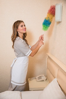 Happy young maid in uniform cleaning the wall light with duster