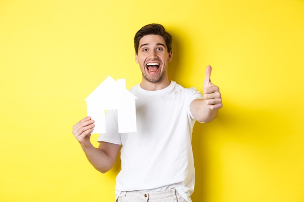 Happy young male buyer showing thumb up and paper house model, smiling satisfied, standing over yellow wall