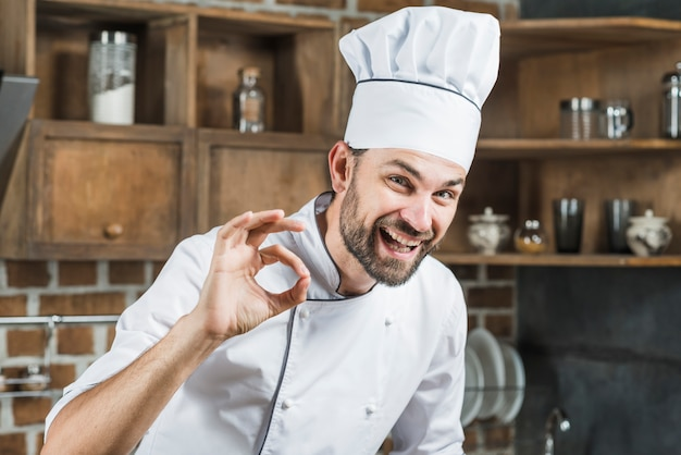 Happy young male chef doing ok sign