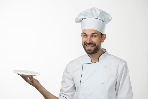 Happy young male chef holding an empty white plate against white backdrop