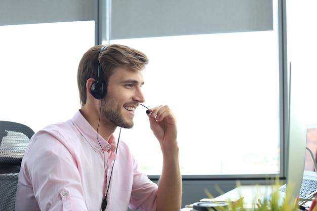 Счастливый молодой мужской руководитель службы поддержки клиентов, работающих в офисе.