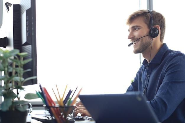 사무실에서 일하는 행복한 젊은 남성 고객 지원 임원.