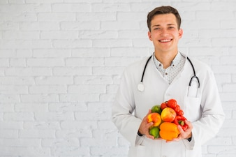 Happy young male doctor standing against the wall holding fresh fruits and vegetable