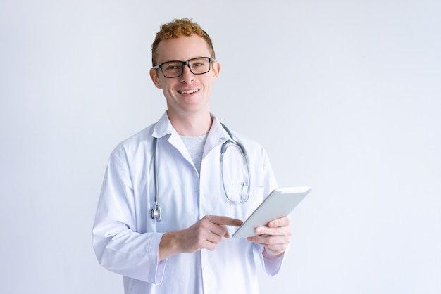 Happy young male doctor using tablet computer