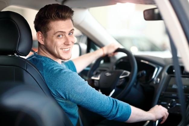 바퀴 뒤에 행복 한 젊은 남성 드라이버 프리미엄 사진