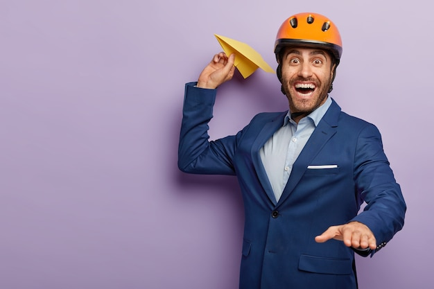 Счастливый молодой инженер-мужчина бросает самолет, носит защитный головной убор и деловой костюм, стремится развивать свой инновационный проект.
