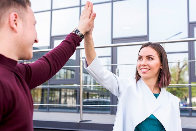 Happy young male and female friend giving high five at outside