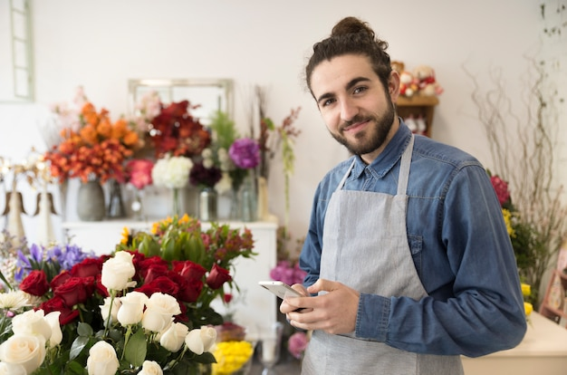Happy young male florist holding mobile phone in hand looking to camera