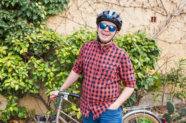 幸せな若い男性は自転車の緑の庭を保持します