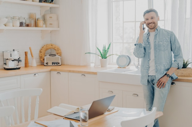 노트북으로 온라인 작업을 하는 동안 부엌에서 즐거운 전화 대화를 나누는 행복한 젊은 남성, 휴대폰으로 고객과 대화하고 성공적인 금융 거래를 제안하는 젊은 남성 기업가