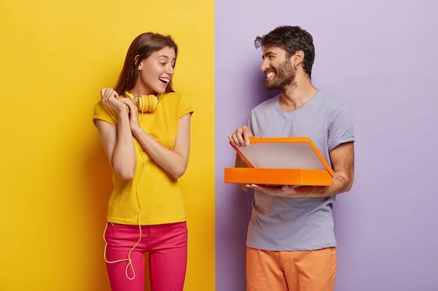 행복한 젊은 남성 모델은 상자를 열고, 생일에 여자 친구를 놀라게하고, 패키지에 무언가를 보여줍니다.