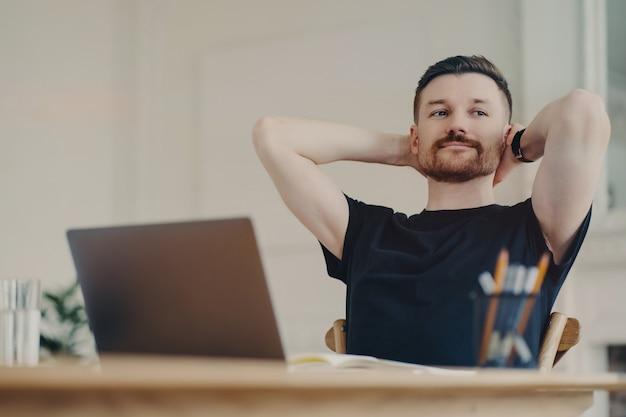 カジュアルな服装で幸せな若い男性サラリーマンは、職場でリラックスし、腕を頭の後ろに置き、脇を向いて笑顔で、ラップトップを持って机に座っています。仕事が終わったので幸せそうに見えるフリーランサー