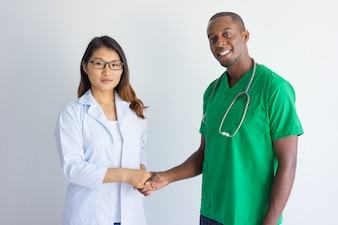 Happy young male physician and female doctor shaking hands.