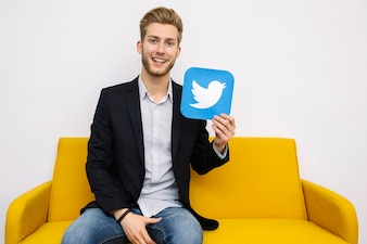 Happy young male sitting on yellow sofa holding twitter icon