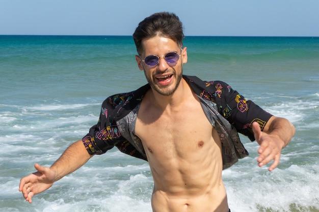 Felice giovane maschio in occhiali da sole divertirsi in spiaggia