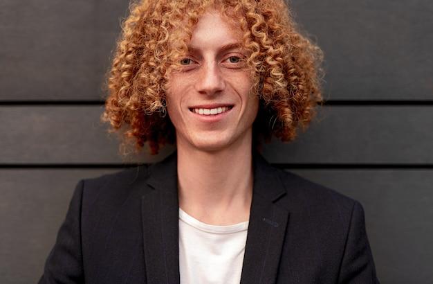 笑顔の巻き毛の生姜髪と幸せな若い男性