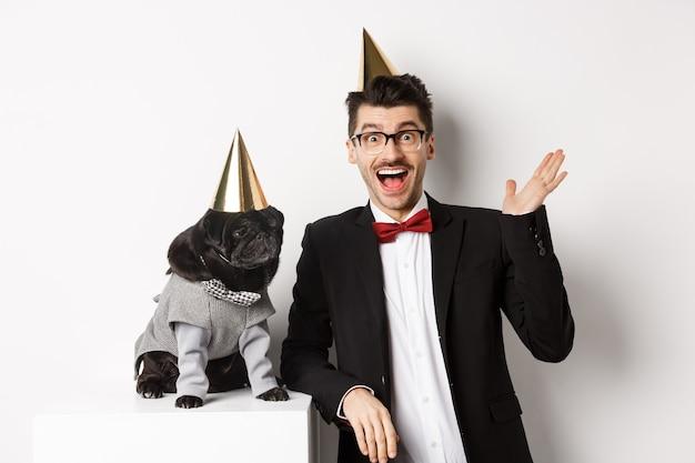행복한 젊은이와 귀여운 검은 개는 파티 콘을 입고 생일을 축하하고, 친근한 인사를 하고 손을 흔들며 흰색 배경 위에 서 있습니다.