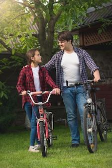 행복 한 젊은 남자와 자전거와 함께 포즈 웃는 소녀