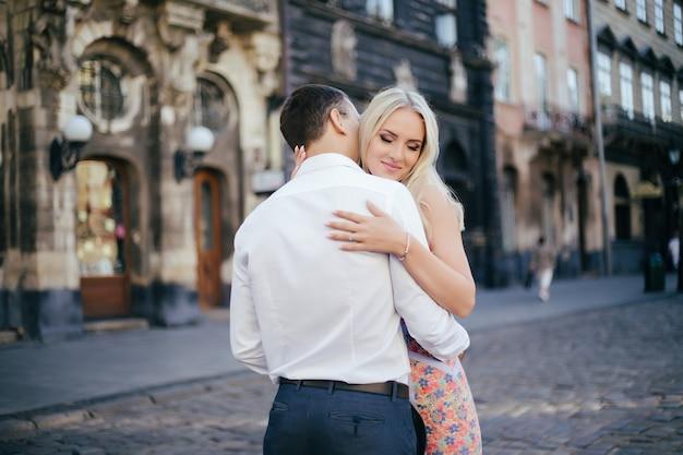 幸せな若い男と通りを歩いて笑顔の女性
