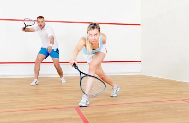 Счастливый молодой мужчина и женщина играют в сквош