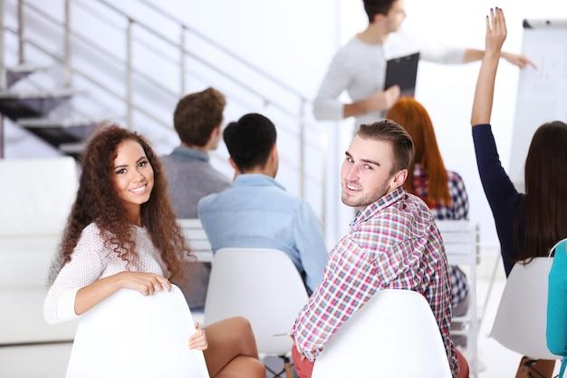 사무실 회의에 다시 앉아 행복 한 젊은 남자와 여자