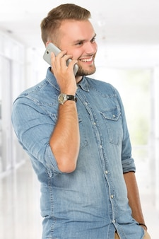 Happy young man answering a phone