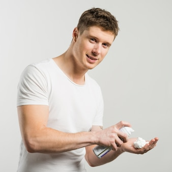 Happy young man applies shaving cream on palm of hand isolated on white backdrop