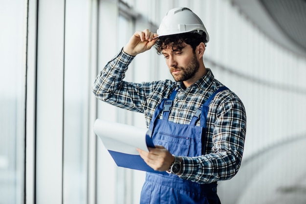 Happy young man architect in hard hat holding folder