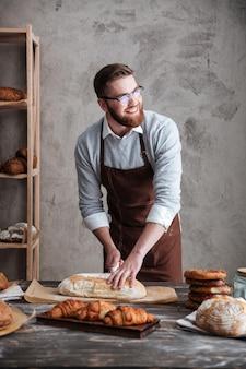 Счастливый пекарь молодого человека стоя на хлебопекарне отрезал хлеб.