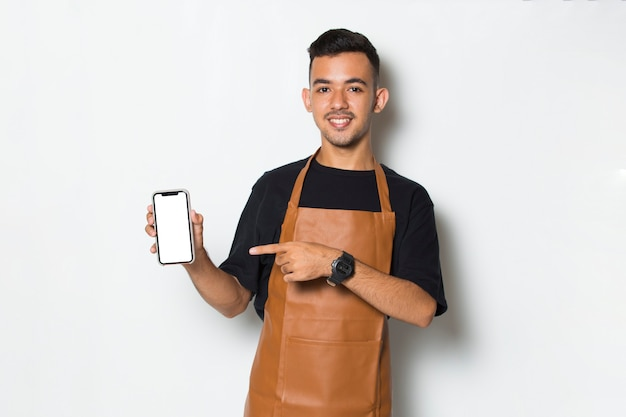 Happy young man barista waitress hold mobile phone with blank empty screen