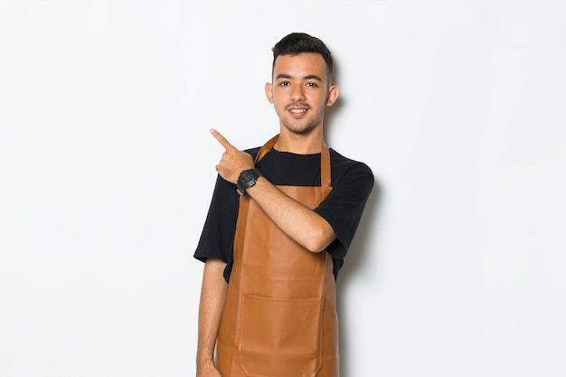 Happy young man barista waitress pointing with fingers to different directions
